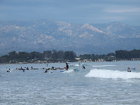 Surfers and mountains behind.