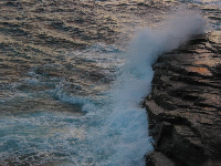 Waves crashing over rocks below.