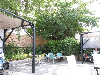 Shade canopies and tall trees in the back of Mister Block Cafe.