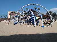 There is some shade in the sand by the playground.