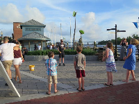 A juggler plays a game with kids at the end of Market Street.