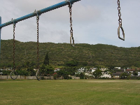 Low mountains, Australian pines, and 1980s houses set the backdrop for the playground and gymnastics rings.