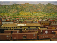 The model railroad with painting of State St and the Santa Ynez mountains behind it.