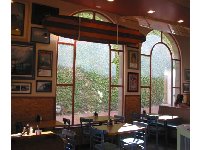The large windows looking out on ivy at PizzaRev.