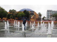Man stands in the fountain at Cesar Chavez Park.