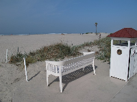 A bench and fancy trash can by the sand at the hotel- notice the overcast tinge to the light.