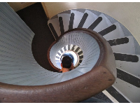 A photographer peeps his head in to take a photo of the spiral stairs.