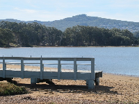 The mini-pier, blue waters, plus strand of trees and hills in the distance. A pretty scene.