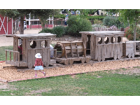 A little girl walks over to the long wooden train.