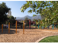 Playground at Libbey Park, with tower and mountains behind.