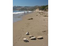 Large, smooth stones sit on the sand at El Capitan Beach.