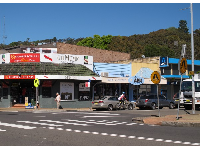 Strip of shops with hills behind.