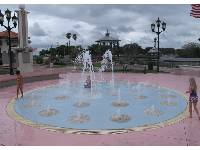Children enjoy the splash pad by the waterfront.
