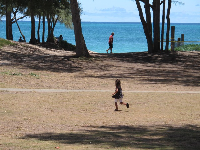 Girl running on the dry grass by the beach.
