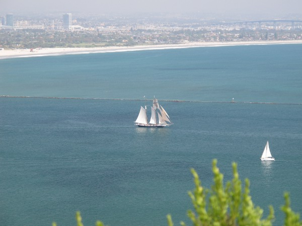 A ship heading out to sea, with Coronado Beach behind. See the Coronado Bridge on the upper right.