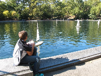 A boy sailing a model boat at Conservation Water.