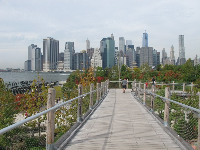 A jogger enjoys the views on the pedestrian bridge down to Brooklyn Bridge Park from Squibb Park.
