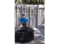 A boy explores stacked tires.