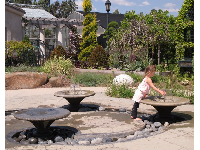 A girl enjoys waterplay in the Children's Garden.