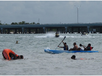 Jet skis, kayak, and raft tipping over, by the causeway.