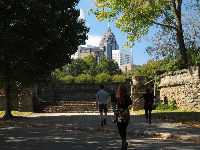 Stone steps that lead up to sports field with view of city skyline.