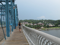 A lady walks across the Walnut Street Bridge.