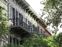 Row of city townhouses with ironwork balconies.