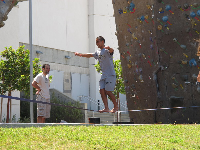A student tightrope walks between the rock-climbing walls.