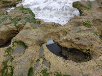Water rushing under rock formations at Carlin Beach.