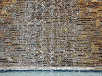 Fountain in front of a layered stone wall.