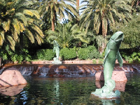 Dolphin statues and tropical gardens, as seen from the sidewalk of The Strip, in front of Mirage Resort.