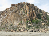 Looking up at Morro Rock from the beach at the far end of Harborwalk.