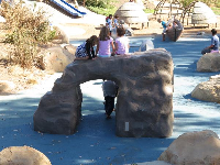 Kids sit atop the rock arch.