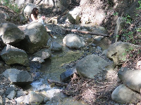 A young woman dries her feet by the creek, which flows from the falls.