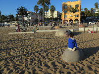 A boy sits on the rounded cement rocks.