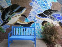 Mosaic wall and blue bench.