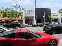 Red sportscar and colorful storefronts.