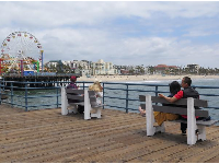 A couple sits at the end of the pier looking toward the ferris wheel.