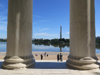 Giant columns, a couple, and Washington Memorial in the distance.