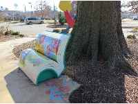 Wizard of Oz bench by a tree.