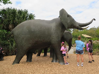 Kids standing by the elephant sculptures.