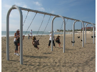 Swings in the sand beside the pier.