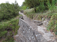 Stone wall supporting the path.