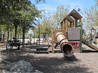 One of many play structures in the center of the park. Shady bench for parents.