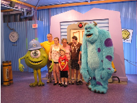 A family greets characters from Monsters Inc.