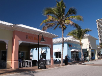 Cafes and shops across from the park in front of the beach.