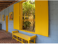 Bold yellow bench and pale blue wall.