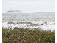 Cruise ship from Port Canaveral, and surfer on the north side of the pier.