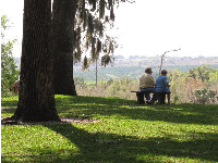 An elderly couple takes in the view of the orange orchards below.