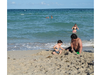 Father and son build a sandcastle.